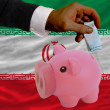 Funding euro into piggy rich bank national flag of iran — Stock Photo