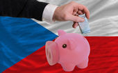 Funding euro into piggy rich bank national flag of czech — Stock Photo