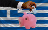 Funding euro into piggy rich bank national flag of greece — Stock Photo