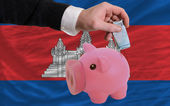 Funding euro into piggy rich bank national flag of cambodia — 图库照片