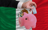 Funding euro into piggy rich bank national flag of mexico — Stock Photo