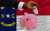 Funding euro into piggy rich bank flag of american state of nort — Stock Photo