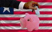 Funding euro into piggy rich bank national flag of liberia — Stock Photo