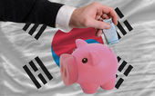Funding euro into piggy rich bank national flag of south korea — Стоковое фото