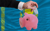 Funding euro into piggy rich bank national flag of kazakhstan — Stock Photo