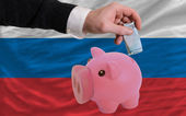 Funding euro into piggy rich bank national flag of russia — Stock Photo
