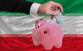 Funding euro into piggy rich bank national flag of iran — 图库照片