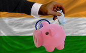 Funding euro into piggy rich bank national flag of of india — Stock Photo
