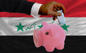 Funding euro into piggy rich bank national flag of iraq — Stock Photo
