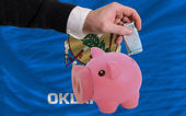 Funding euro into piggy rich bank flag of american state of okla — Стоковое фото