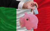 Funding euro into piggy rich bank national flag of italy — Stock Photo