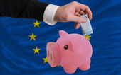 Funding euro into piggy rich bank national flag of europe — Stock Photo