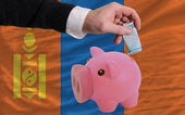 Funding euro into piggy rich bank national flag of mongolia — Stock Photo