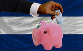 Funding euro into piggy rich bank national flag of nicaragua — Stock Photo