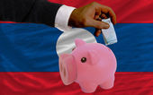 Funding euro into piggy rich bank national flag of laos — Stock Photo