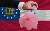 Funding euro into piggy rich bank flag of american state of geor — Stock Photo