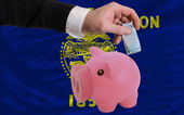 Funding euro into piggy rich bank flag of american state of oreg — Stock Photo
