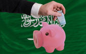 Funding euro into piggy rich bank national flag of of saudi ara — Stock Photo
