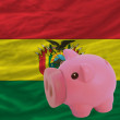 Piggy rich bank and  national flag of bolivia — Stock Photo