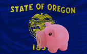 Piggy rich bank and flag of american state of oregon — Stock Photo