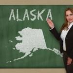 Teacher showing map of alaska on blackboard — Stock Photo #25257227