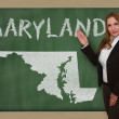 Teacher showing map of maryland on blackboard - Stock Photo