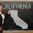 Teacher showing map of california on blackboard — Stock Photo