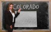 Teacher showing map of colorado on blackboard — Stock Photo