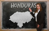 Teacher showing map of honduras on blackboard — Stock Photo