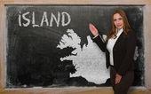 Teacher showing map of iceland on blackboard — Stock Photo