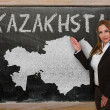 Teacher showing map of kazakhston blackboard — Stock Photo #25353631