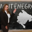 Stock Photo: Teacher showing map of montenegro on blackboard