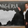 Teacher showing map of nigeria on blackboard — Stock Photo