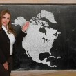 Teacher showing map of north america on blackboard — Stock Photo #25381055