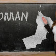 Stock Photo: Teacher showing map of oman on blackboard