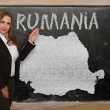 Stock Photo: Teacher showing map of romanion blackboard