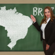 Teacher showing map of brazil on blackboard — Stock Photo