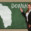 Teacher showing map of dominica on blackboard — Stock Photo