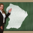 Teacher showing map of french guiana on blackboard — Stock Photo