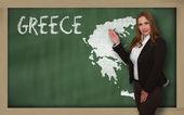 Teacher showing map of greece on blackboard — Stock Photo
