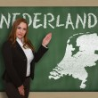 Teacher showing map of netherlands on blackboard — Stock Photo