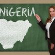 Teacher showing map of nigeria on blackboard — Stock Photo #25664419