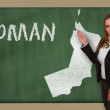 Teacher showing map of oman on blackboard — Stock Photo