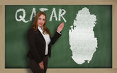 Teacher showing map of qatar on blackboard — Stock Photo