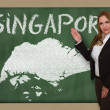 Stock Photo: Teacher showing map of singapore on blackboard