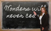 Teacher showing Wonders will never cease on blackboard — Стоковое фото