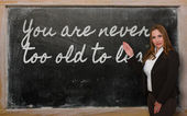 Teacher showing You are never too old to learn on blackboard — Стоковое фото