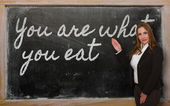 Teacher showing You are what you eat on blackboard — Stock Photo