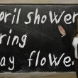 Teacher showing April showers bring May flowers on blackboard — Stock Photo #25829405