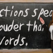 Stock Photo: Teacher showing Actions speak louder thwords on blackboard